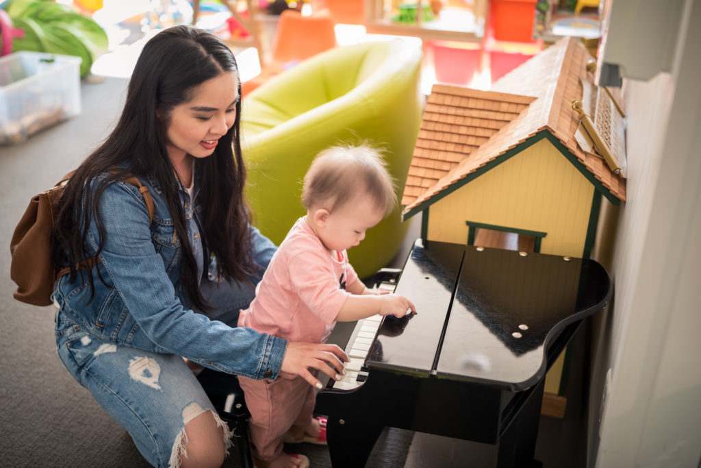 Glamouraspirit and Adelina playing piano inside RMHBC in Vancouver building