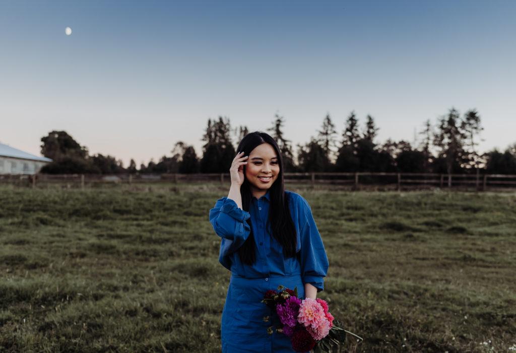posing with dahlia flowers at Alpaca farm