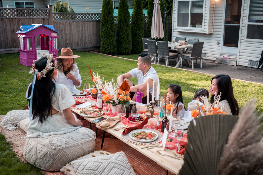 friends at Glamouraspirit home for dinner backyard picnic to benefit families at RMH BC enjoying a good time chatting and eating